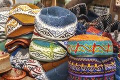Tocados asiáticos tradicionales de un fieltro multicolor con un hilo coloreado bordado del ornamento nacional imágenes de archivo libres de regalías