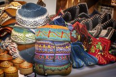 Tocados asiáticos tradicionales de un fieltro multicolor con un hilo coloreado bordado del ornamento nacional Foco selectivo imagen de archivo libre de regalías