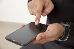 Tocando em um telefone esperto Imagem de Stock