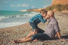Tocando la escena atractiva del padre y del hijo disfrute de las vacaciones de verano junto que juegan en la playa de piedra que  Fotos de archivo