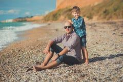 Tocando la escena atractiva del padre y del hijo disfrute de las vacaciones de verano junto que juegan en la playa de piedra que  Imagen de archivo libre de regalías