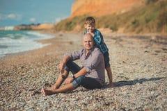 Tocando la escena atractiva del padre y del hijo disfrute de las vacaciones de verano junto que juegan en la playa de piedra que  Fotografía de archivo