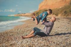 Tocando la escena atractiva del padre y del hijo disfrute de las vacaciones de verano junto que juegan en la playa de piedra que  Imágenes de archivo libres de regalías