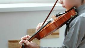 Tocar el violín Siete años irreconocibles del muchacho que juega el primer del violín almacen de metraje de vídeo