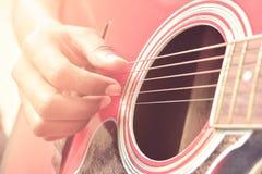 Tocar la guitarra acústica imagen de archivo