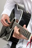 Tocar la guitarra acústica Imágenes de archivo libres de regalías