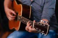 Tocar la guitarra acústica Fotos de archivo libres de regalías