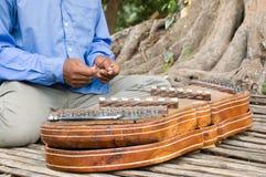 Tocar un instrumento musical del khim, Camboya Imagenes de archivo