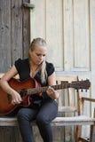 Tocar una guitarra acústica Imagen de archivo