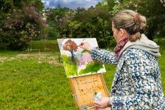 Tocchi finali contemplativi femminili del paintig del pittore all'aperto Fotografia Stock Libera da Diritti