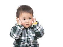 Tocco del neonato dell'Asia il suo orecchio fotografie stock libere da diritti