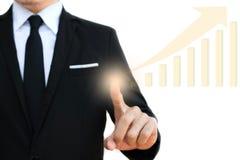 Tocco dell'uomo d'affari sullo schermo vitual con i grafici finanziari che mostrano reddito crescente immagine stock