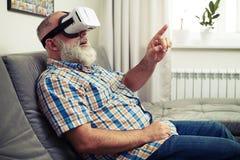 Tocco dell'uomo senior qualcosa con il suo dito facendo uso dei vetri di VR Fotografie Stock