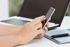 Tocco della mano sul telefono nero sullo scrittorio Immagini Stock