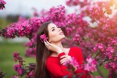 Tocco della primavera La giovane donna bella felice in vestito rosso gode dei fiori e della luce rosa freschi del sole nel parco  Fotografie Stock