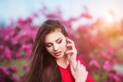 Tocco della primavera La giovane donna bella felice in vestito rosso gode dei fiori e della luce rosa freschi del sole nel parco  Fotografia Stock