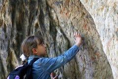 Tocco della ragazza una roccia del granito all'aperto Fotografie Stock