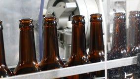 Tocco robot Primo piano sparato di una macchina di produzione in fabbrica di birra Bottiglie di birra vuote sul trasportatore Rig video d archivio