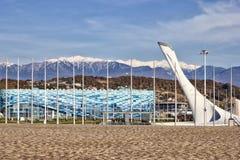 Tocha olímpica, o palácio de esportes de inverno e montanha Fotos de Stock Royalty Free