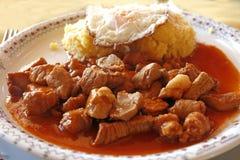 Tochitura is een traditionele Roemeense die schotel van rundvlees wordt gemaakt en varkensvlees met eieren en polenta wordt gedie Stock Foto