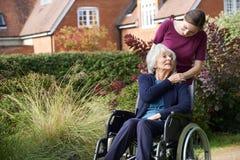 Tochter, die ältere Mutter im Rollstuhl drückt stockfotografie