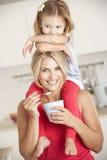 Tochter, die auf Schultern sitzt, während Mutter Jogurt isst Stockbilder