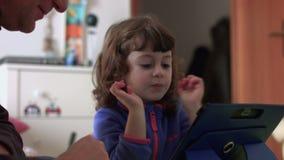 Tochter, die das Scherzen und das Gewinnen auf einer Tablette SF spielt stock video footage