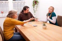 Tochter, die in den Kartenspielen mit Familie betrügt Stockfoto