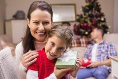 Tochter, die ein Geschenk mit ihrer Mutter hält Stockfotos