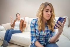 Tochter, die ein Telefon schaut und ihre Mutter ignoriert Stockfotos