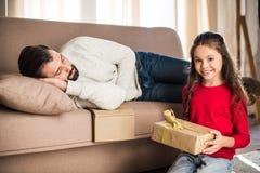 Tochter, die Geschenkbox während Vaterschlafen hält lizenzfreie stockbilder