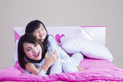 Tochter, die ihre Mutter auf Bett umfasst Stockfotos