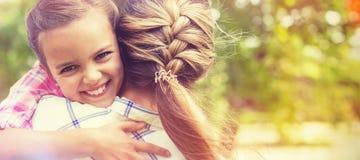 Tochter, die ihre Mutter im Park umfasst Stockfotos