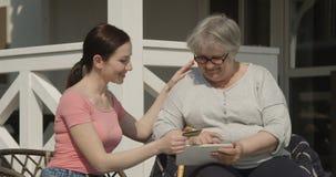 Tochter, die ihrer älteren Mutter hilft, das Internet-Kaufen zu verwenden on-line mit der Kreditkarte zusammen draußen lächelt au stock footage