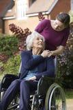 Tochter, die ältere Mutter im Rollstuhl drückt Stockbild