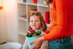 Tochter, die lustiges Gesicht macht, nachdem rote Blumen mit Mutter gerochen worden sind stockbilder