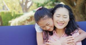 Tochter, die Mutter hinten im Garten 4k umarmt stock video