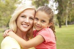 Tochter, die Mutter im Park umarmt stockfoto