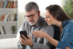 Tochter, die wie man ein Telefon zu ihrem Vater unterrichtet, benutzt lizenzfreies stockfoto