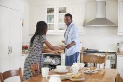 Tochter-helfender Vater To Clear Table nach Familien-Mahlzeit lizenzfreies stockbild