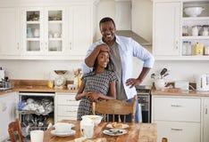 Tochter-helfender Vater To Clear Table nach Familien-Mahlzeit stockbilder
