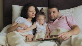 Tochter mit der Familie, die ein Buch im Bett liest stock video footage