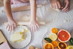 Tochter mit Mutter kneten Teig für Kekse Stockbild