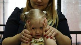 Tochter spielt Büffelleder des Blinders s und rüttelt ihren Kopf, während sie auf ihrem Schoss der Mutter s sitzt stock video footage