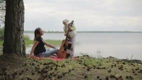 Tochter spielt die Gitarre für seine Mutter auf dem Ufer des Sees im wolkigen Wetter stock video