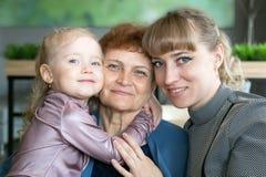 Tochter und Enkelinumarmungs- und -kussgro?mutter stockbilder