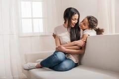 Tochter und lächelnde Mutter, die sich zu Hause umarmen Stockfoto