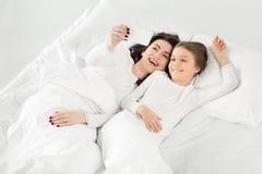 Tochter und Mutter, die selfie auf Smartphone beim Lügen auf Bett nehmen Stockfotografie