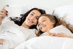 Tochter und Mutter, die selfie auf Smartphone beim Lügen auf Bett nehmen Stockbilder