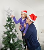 Tochter und Vater Decorating Christmas Tree Stockfoto